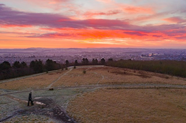 Sunrise over a dog walker on the hills above the town. Photo: Paul Atherley