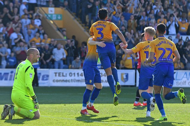 Mansfield's players celebrate Mal Benning's most famous goal for the club as he shoots down Chesterfield away from home in April 2019.