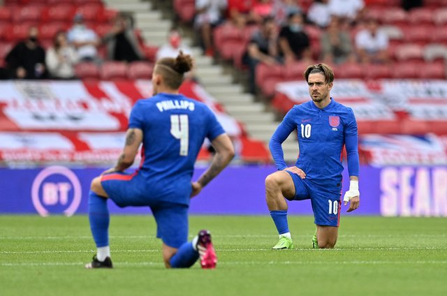 England players Kalvin Phillips and Jack Grealish take the knee before the friendly with Romania at the Riverside on Sunday.  (Photo by PAUL ELLIS/POOL/AFP via Getty Images)