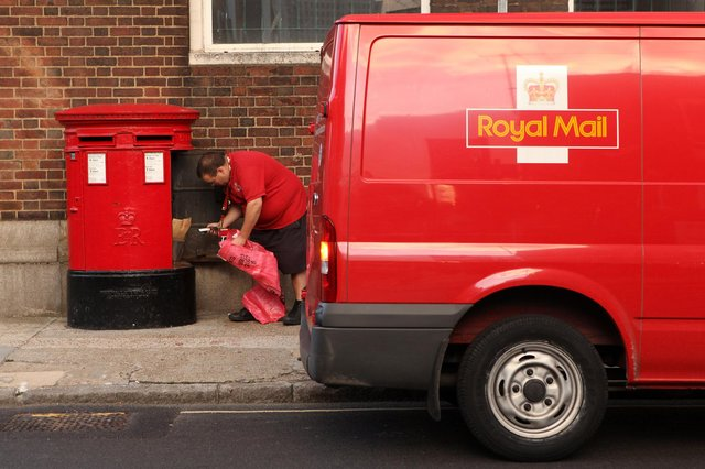 A Royal Mail employee empties a post box  (Photo by Oli Scarff/Getty Images)
