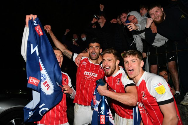 Players and fans of Cheltenham Town celebrate their side's victory outside the ground after gaining promotion to the Sky Bet League One.